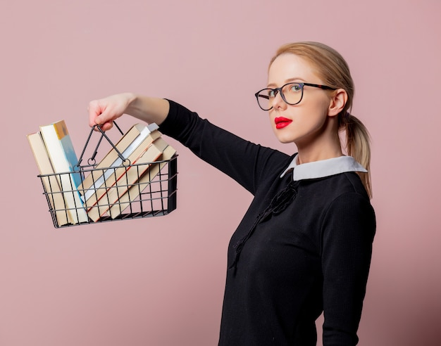 Blonde woman black dress and glasses hold shopping basket with books on pink background