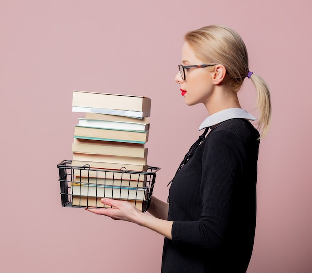 Blonde woman black dress and glasses hold shopping basket with books on pink wall