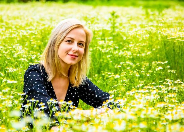 Blonde woman in black dress is sitting on chamomiles flowers field