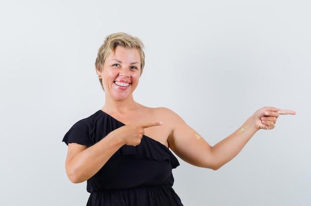 Donna bionda in abito nero che punta a destra con le dita indice e sorridente e guardando ottimista