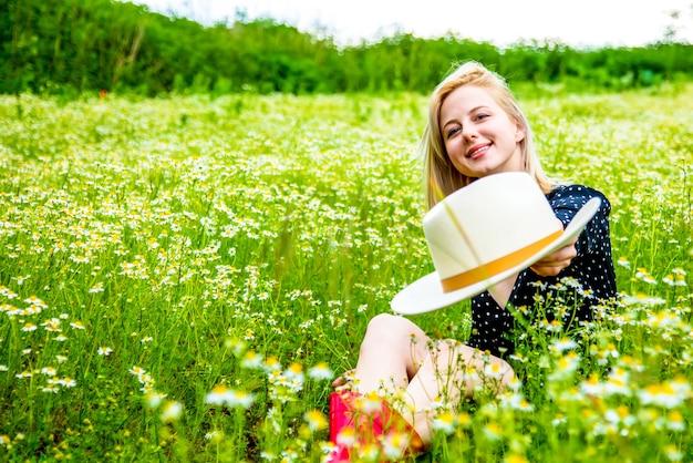 Blonde woman in black dress sitting on chamomiles flowers field