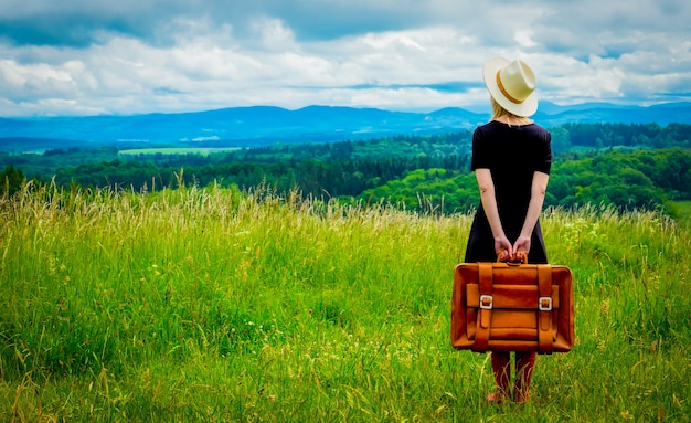 Blonde woman in black dress and suitcase at meadow with mountains behind