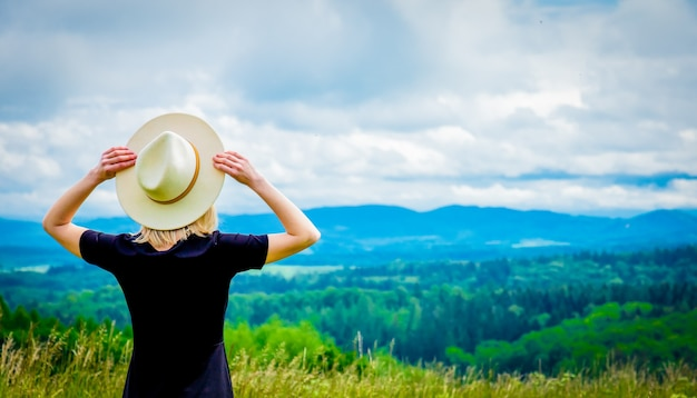 Blonde woman in black dress and white hat at meadow with mountains behind