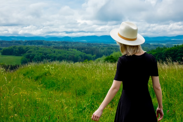 Blonde woman in black dress and white hat at meadow with mountains