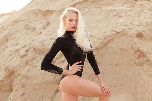 Blonde woman in black slim bodysuit posing in the sand ground.