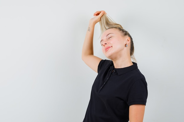 Donna bionda in maglietta nera che tiene i suoi capelli e che sembra felice