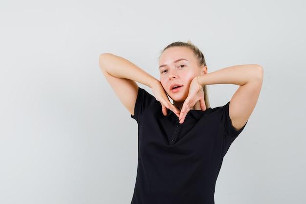 Donna bionda in maglietta nera che mette le mani sotto il mento