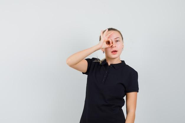 Donna bionda in maglietta nera che mostra segno giusto e che sembra ottimista