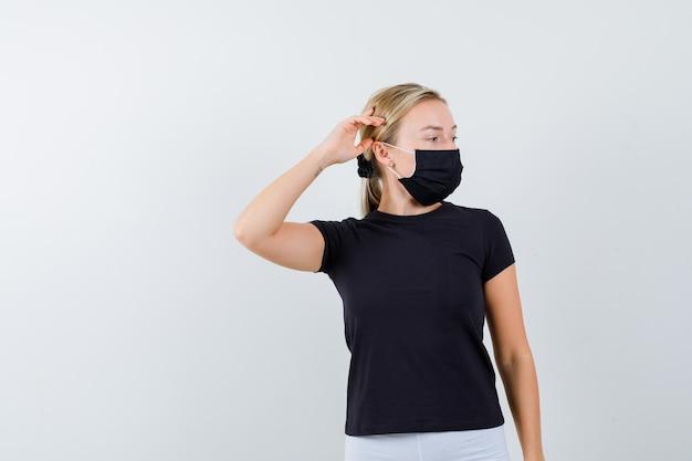 Donna bionda in maglietta nera, pantaloni bianchi, maschera nera che tiene la mano vicino all'orecchio