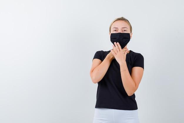 Donna bionda in maglietta nera, pantaloni bianchi, maschera nera che si tiene per mano davanti al collo