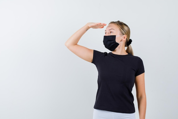 Blonde woman in black t-shirt, white pants, black mask looking far away