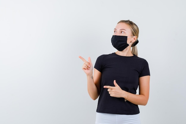 Blonde woman in black t-shirt, white pants, black mask pointing left with index fingers