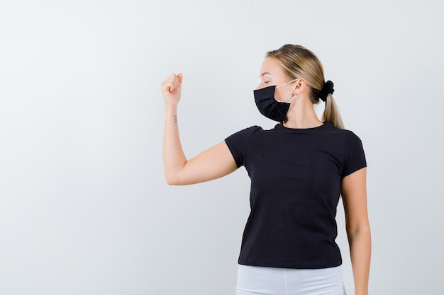 Blonde woman in black t-shirt, white pants, black mask showing muscles