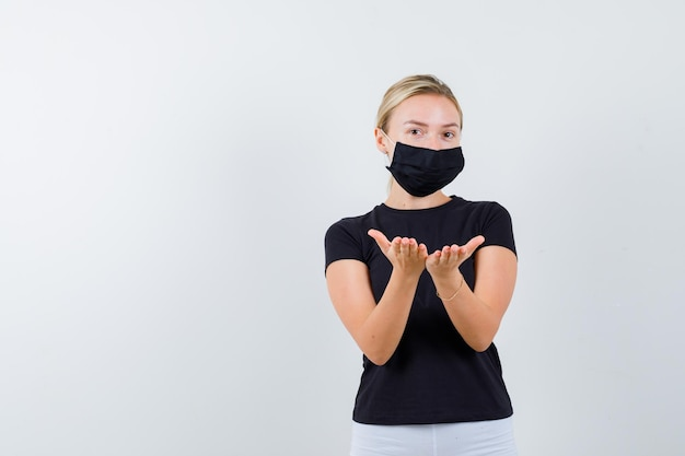 Blonde woman in black t-shirt, white pants, black mask stretching cupped hands and looking serious