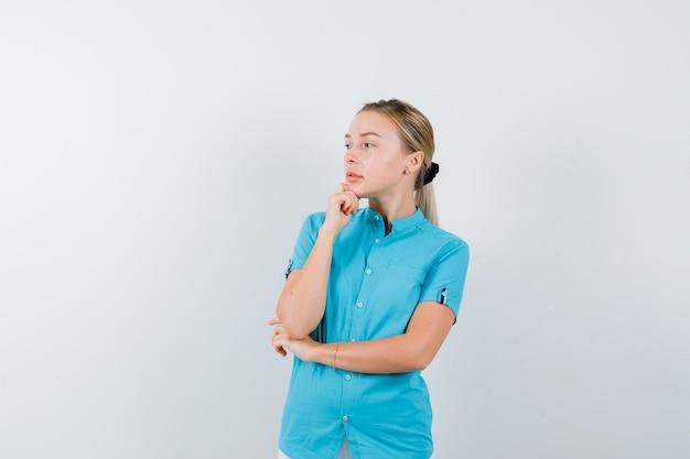 Donna bionda in camicetta blu che sostiene il mento a portata di mano e sembra pensierosa isolata