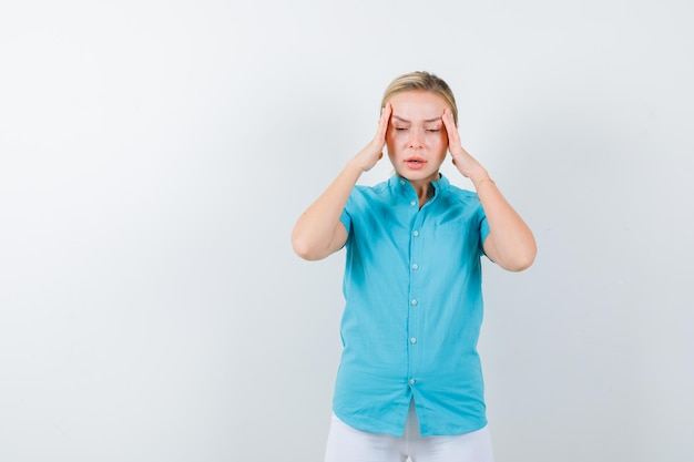 Blonde woman in blue blouse rubbing temples and looking depressed isolated