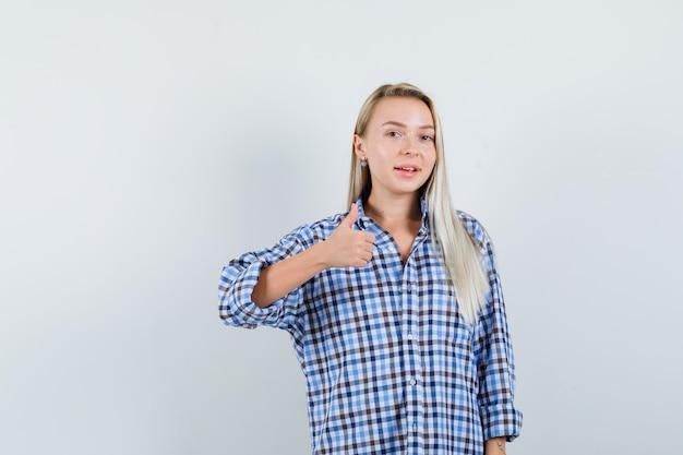 Donna bionda in camicia a quadretti blu percalle che mostra pollice in su e che sembra felice, vista frontale.
