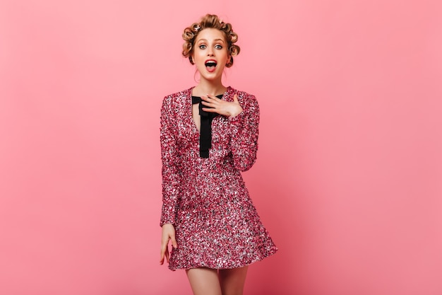 Blonde woman in brilliant outfit looks at front in amazement on pink wall