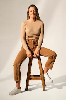 Blonde woman in brown casual outfit sitting on a chair