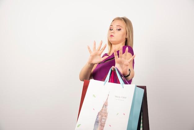 ショッピングバッグの束を運ぶ金髪の女性。