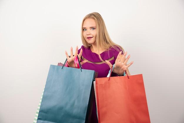 困惑した表情でカラフルな買い物袋を運ぶ金髪の女性。