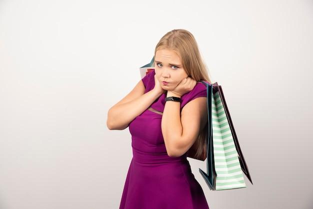 白で買い物袋を運ぶ金髪の女性。