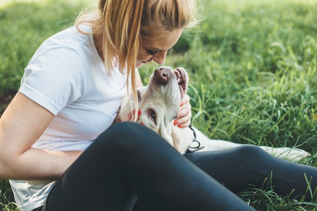 Blonde woman in casual clothes playing on the grass with her labrador embracing and kissing it