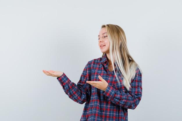 Donna bionda in camicia a quadri tenendosi per mano come tenendo qualcosa e guardandolo e guardando felice, vista frontale.