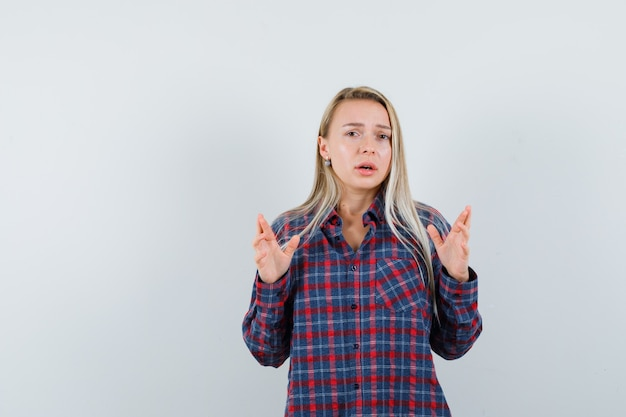 Blonde woman in checked shirt raising hands like explaining something and looking displeased , front view.