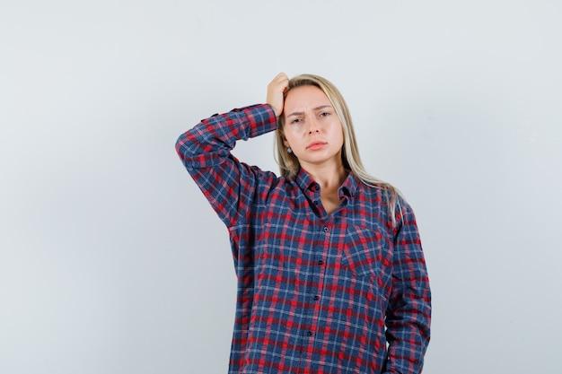 Donna bionda in camicia a quadri in piedi nella posa di pensiero, tenendo la mano sulla testa e guardando pensieroso, vista frontale.