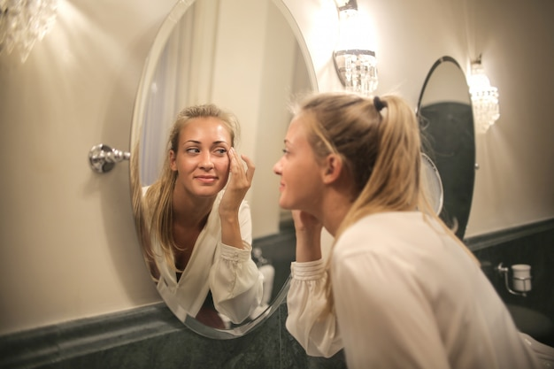 Blonde woman checking herself in the mirror