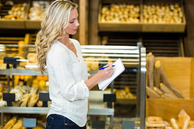 Блондинка женщина список проверки в супермаркете