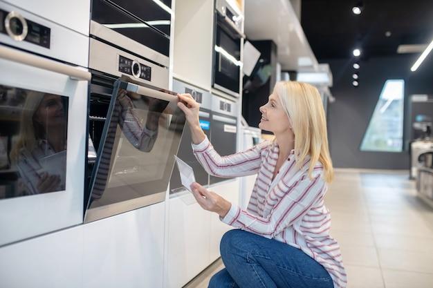 メガストアでオーブンを選ぶ金髪の女性