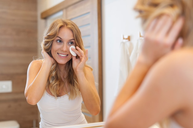 Blonde woman cleaning face in front of mirror