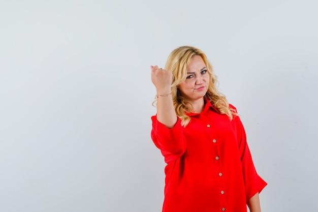 Donna bionda che stringe il pugno in camicetta rossa e sembra carina. vista frontale.