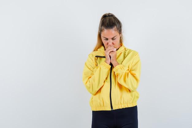 拳を握りしめ、黄色のボンバージャケットと黒のズボンで祈りのポーズで立って集中して見えるブロンドの女性