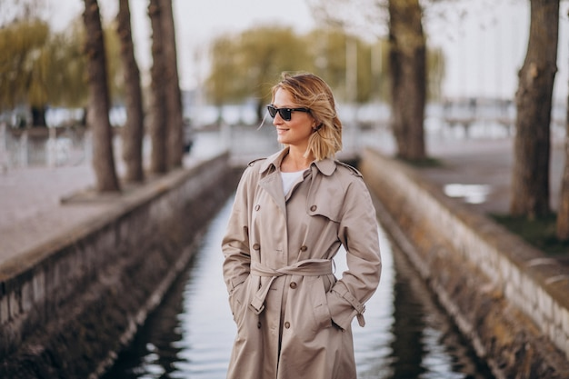 Blonde woman in coat outside in park