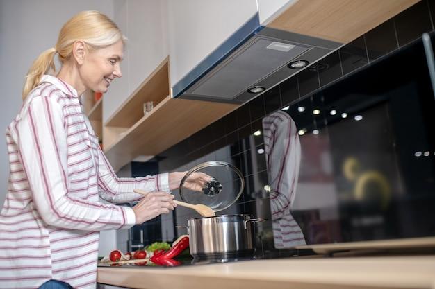 キッチンで料理と前向きな気持ちのブロンドの女性
