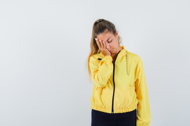 Blonde woman covering eye with hand in yellow bomber jacket and black pants and looking harried