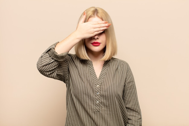 Blonde woman covering eyes with one hand feeling scared or anxious, wondering or blindly waiting for a surprise