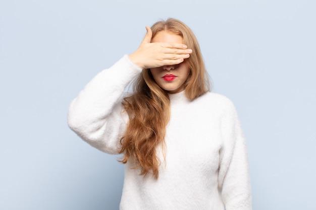 무서워하거나 불안한 한 손으로 눈을 덮고있는 금발의 여자