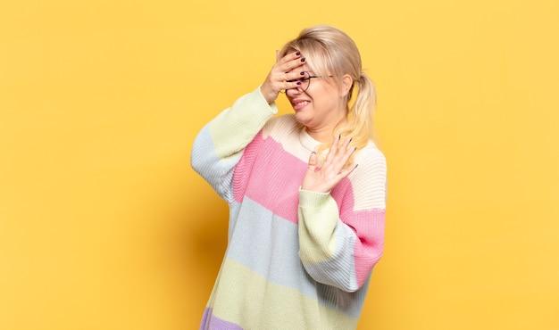 Блондинка закрывает лицо рукой и выставляет другую руку вперед, чтобы остановиться, отказываясь от фотографий или изображений