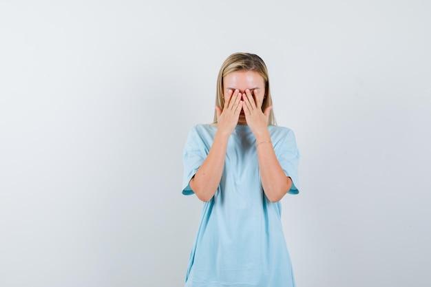 파란색 티셔츠에 손으로 얼굴을 덮고 부끄러워 보이는 금발의 여자