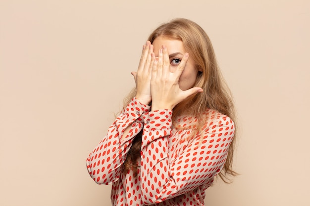 Blonde woman covering face with hands, peeking between fingers with surprised expression
