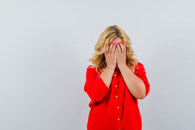 Blonde woman covering face with hands in red blouse and looking dismal. front view.