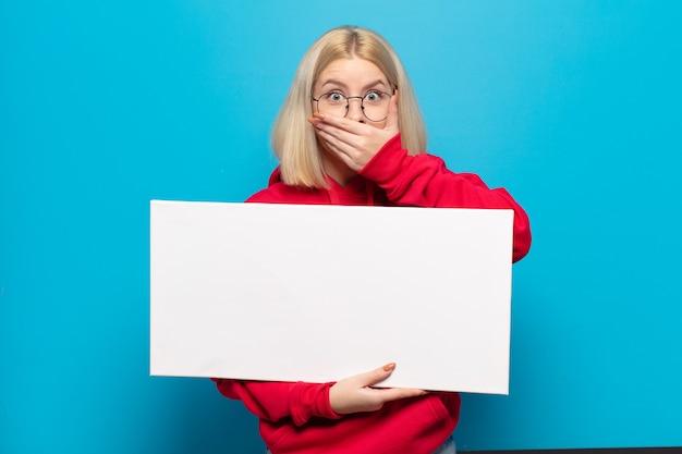 Блондинка закрывает рот руками с шокированным, удивленным выражением лица, хранит секрет или говорит: ой