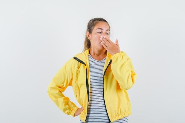Donna bionda che copre la bocca con le mani in bomber giallo e camicia a righe e sembra sorpreso