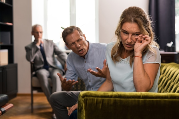 Blonde woman crying while her husband shouting at her in the presence of their psychotherapist