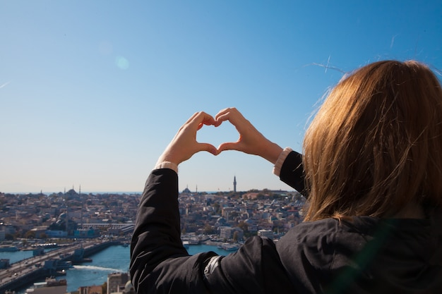Blonde woman in dark coat standing with hands up making a heart on the observation deck with bosphorus and istanbul city view