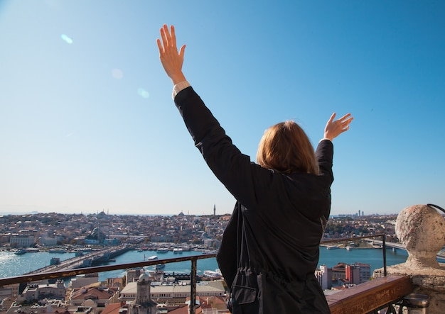 Blonde woman in dark coat standing with hands up on the observation deck with bosphorus and istanbul city view